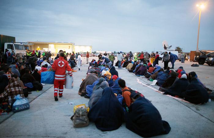 Беженцы ожидают отправки в Вену у австро-венгерской границы в населенном пункте Никельсдорф