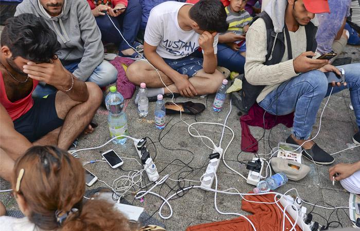 Мигранты заряжают мобильные телефоны у здания вокзала в Будапеште