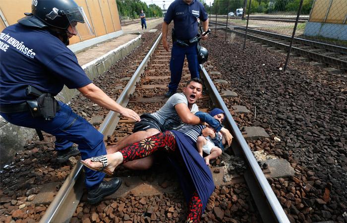 Полицейские пытаются задержать семью беженцев в городе Бичке, Венгрия