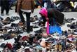 Женщина ищет обувь среди вещей, пожертвованных жителями в германском Дортмунде
