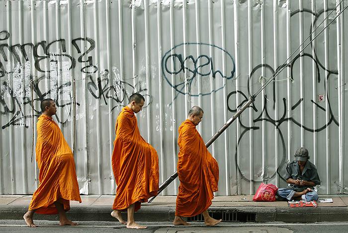 Монахи бредут мимо продавца амулетов по утреннему Бангкоку