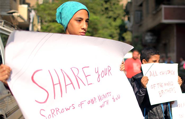 Дети стоят с плакатами возле морга в Каире, где находятся тела жертв авиакатастрофа А321