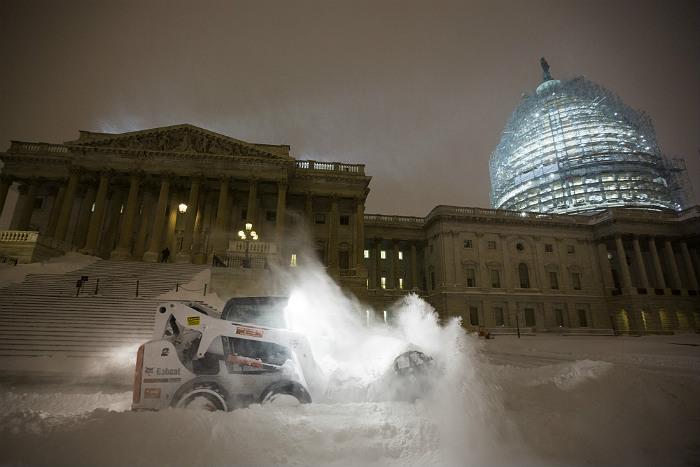 Снегоуборочная машина чистит улицу перед Капитолием в Вашингтоне
