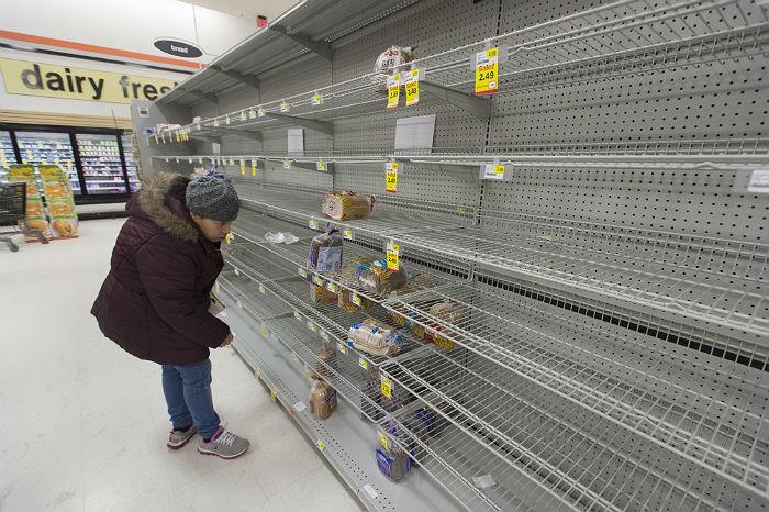 Покупатель перед пустыми полками супермаркета в городе Александрия, штат Виргиния. Жители восточного побережья США запасаются продуктами и товарами первой необходимости в преддверии снежной бури.