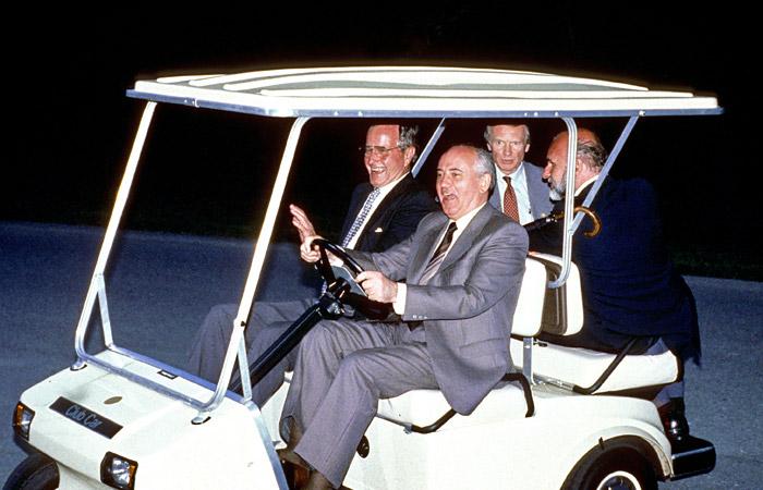 """Президент США Джордж Буш (слева) и Михаил Горбачев, который пытается совладать с каром для гольфа в """"Кэмп Дэвид"""", где проходили летние переговоры в июне 1990 года"""
