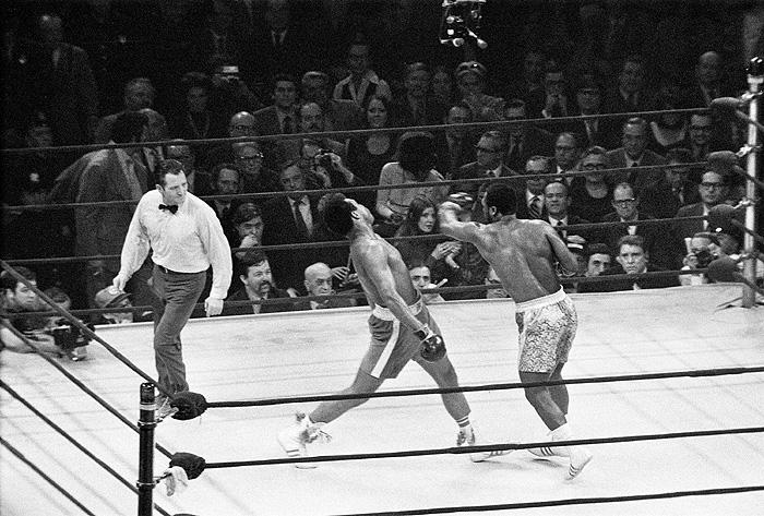 """Джо Фрейзер наносит удар Мохаммеду Али в ходе первого из трех их поединков в """"Мэдисон-Сквер-Гарден"""" в 1971 году. Журналисты окрестили эту встречу """"Боем века"""". Фрейзер одержал победу, а Али потерпел первое в карьере поражение. Второй бой остался за Али, а третий - легендарная """"Мясорубка в Маниле"""" - был остановлен по требованию тренера Фрейзера."""