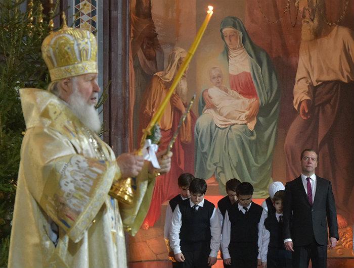 Патриарх Московский и всея Руси Кирилл (слева) и премьер-министр РФ Дмитрий Медведев (справа на втором плане) во время праздничного богослужения по случаю Рождества Христова в храме Христа Спасителя в Москве