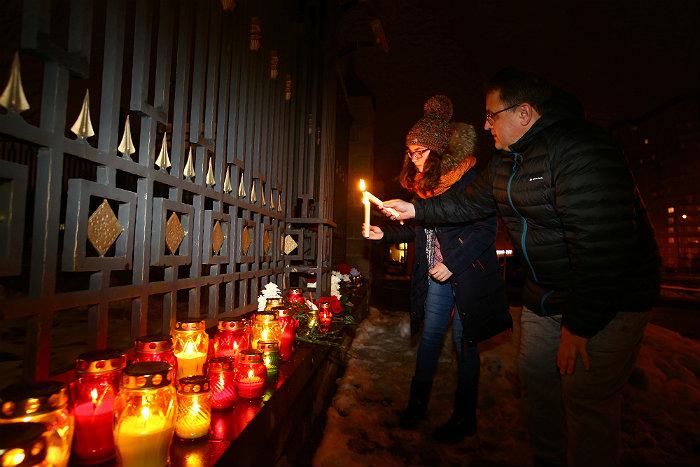 Жители Минска приносят свечи и цветы к российскому посольству