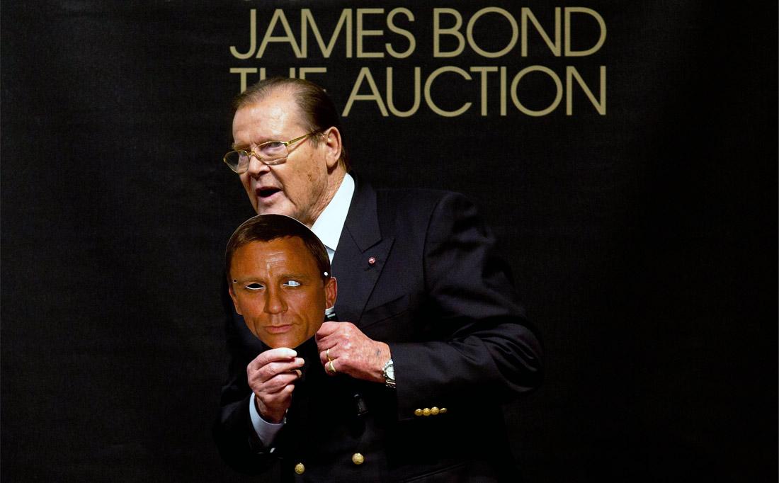 Актер Роджер Мур держит в руках маску с изображением Дэниэла Крэйга на аукционе, посвященном 50-летнему юбилею Бондианы