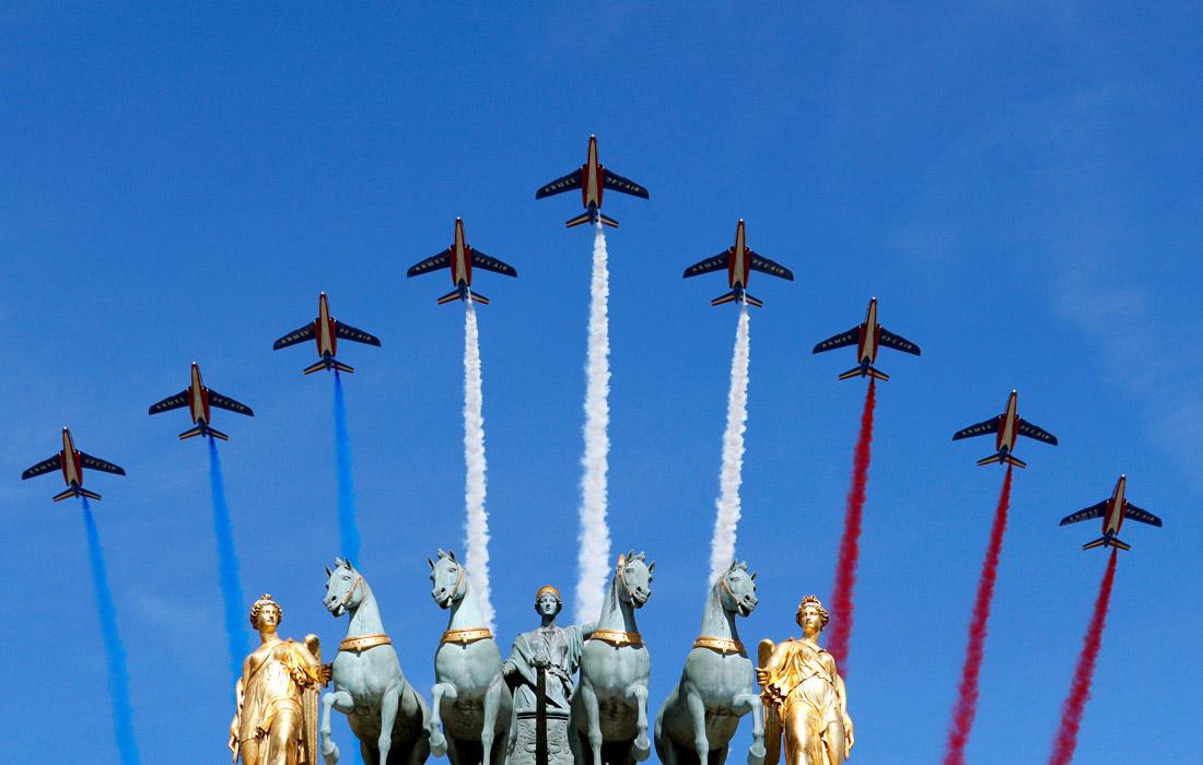 """Самолеты """"Альфа Джет"""" пилотажной группы """"Патруль де Франс"""" выпускают дым с цветами национального флага над Триумфальной аркой"""
