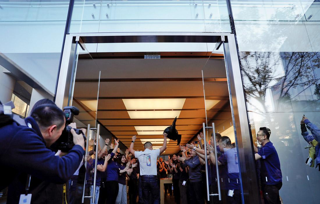 Работники магазина в Пекине приветствуют первого покупателя нового iPhone
