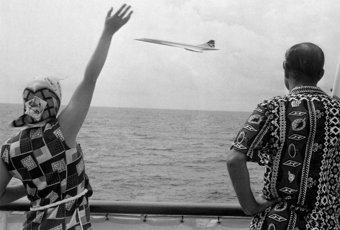 """Королева машет пролетающему лайнеру """"Конкорд"""" с борта яхты """"Британия"""" у Барбадоса. 1977 год."""
