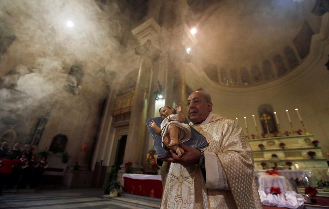 Священник держит статуэтку младенца Иисуса во время рождественской мессы в Каире, Египет