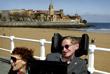 Тяжелое заболевание, почти на 40 лет приковавшее ученого к инвалидному креслу, не помешало ему вести активный образ жизни, много путешествовать и продолжать свои научные исследования. На фото: Стивен Хокинг с женой Элайн на пляже Сан-Лоренцо в испанском городе Хихон в апреле 2005 года.