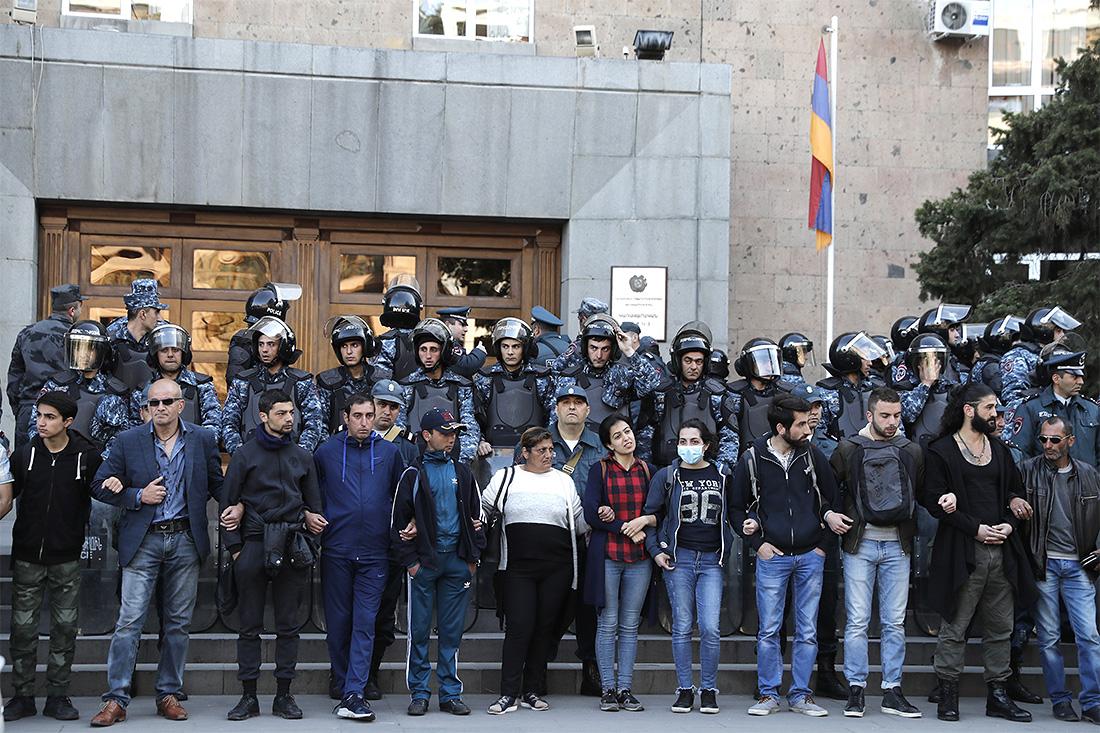 Здания окружены спецподразделениями полиции. Перед ними в ряд выстроились демонстранты, чтобы не пропустить сотрудников госведомств и министерств на свои рабочие места.