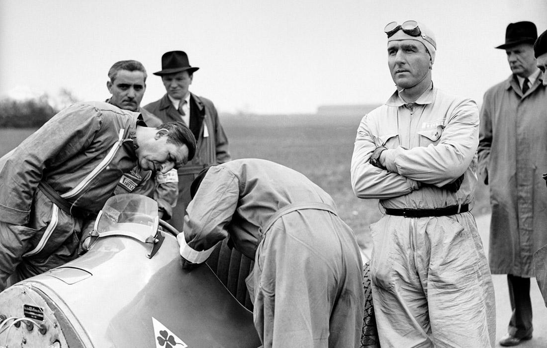 """Итальянец Джузеппе Фарина (стоит второй справа) - победитель первого Гран-при """"Формулы-1"""" в истории, фото датировано маем 1950 года. В """"Формуле-1"""" выступал до 1956 года включительно, а через 10 лет погиб, попав в ДТП по пути на Гран-при Франции."""