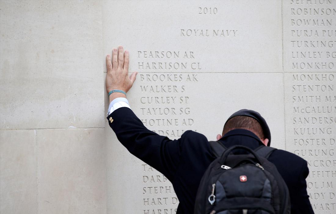 Мужчина у стены Национального мемориального дендрария в Лондоне