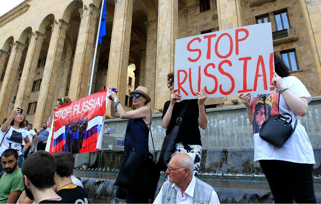 Протестующие рядом со зданием парламента держат антироссийские плакаты