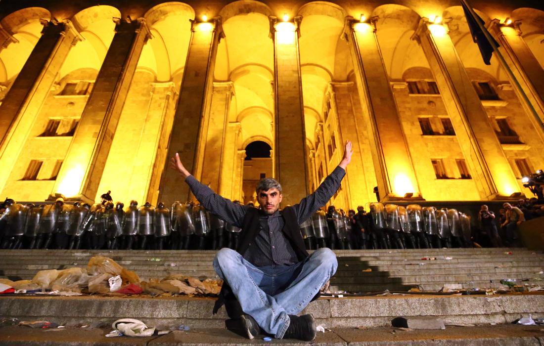 Участник митинга позирует на ступенях парламента перед полицейским оцеплением