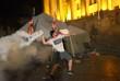 Участник протестов бросает дымовую шашку в полицейское оцепление у здания парламента