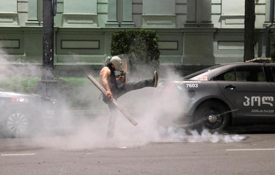 Протестующий на проспекте Руставели в противогазе, с дубиной и полицейским щитом