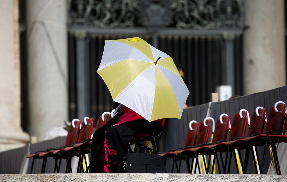 Член духовенства спасается от палящего солнца под зонтом на площади Святого Петра в Ватикане