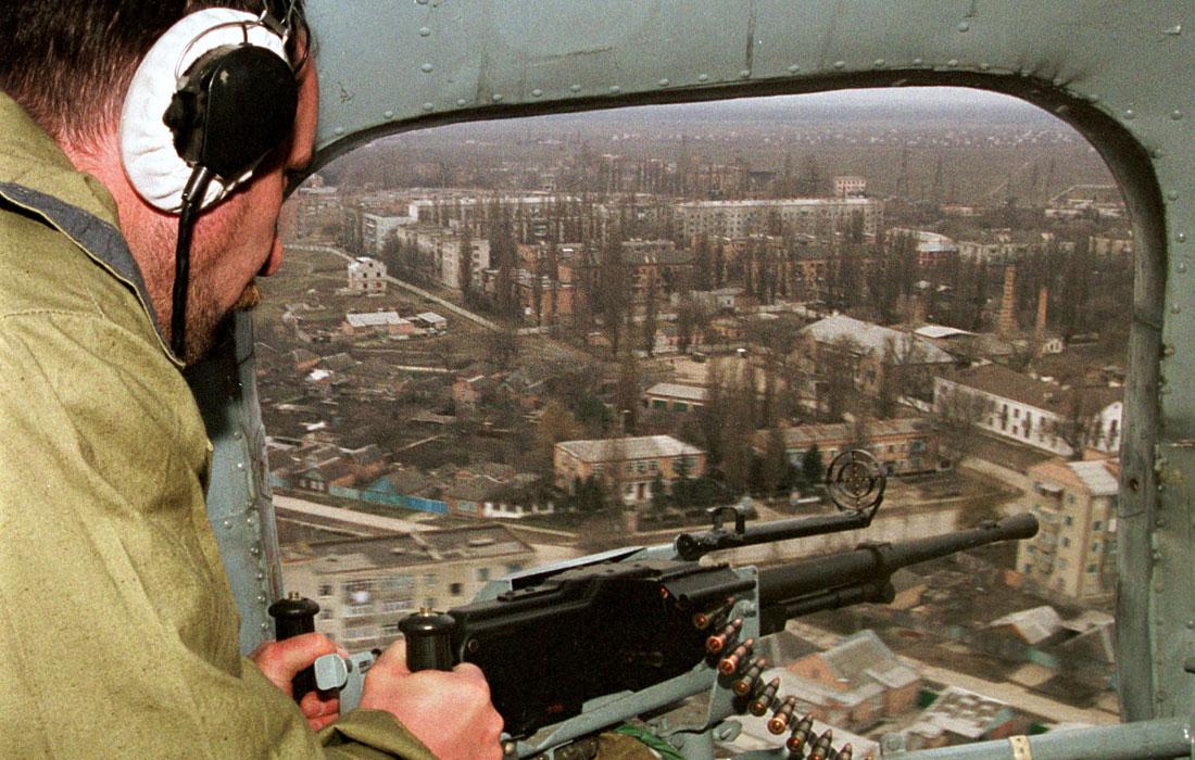 Российский вертолет со стрелком на борту пролетает над столицей Чечни Грозным. 26 января 2000 год.