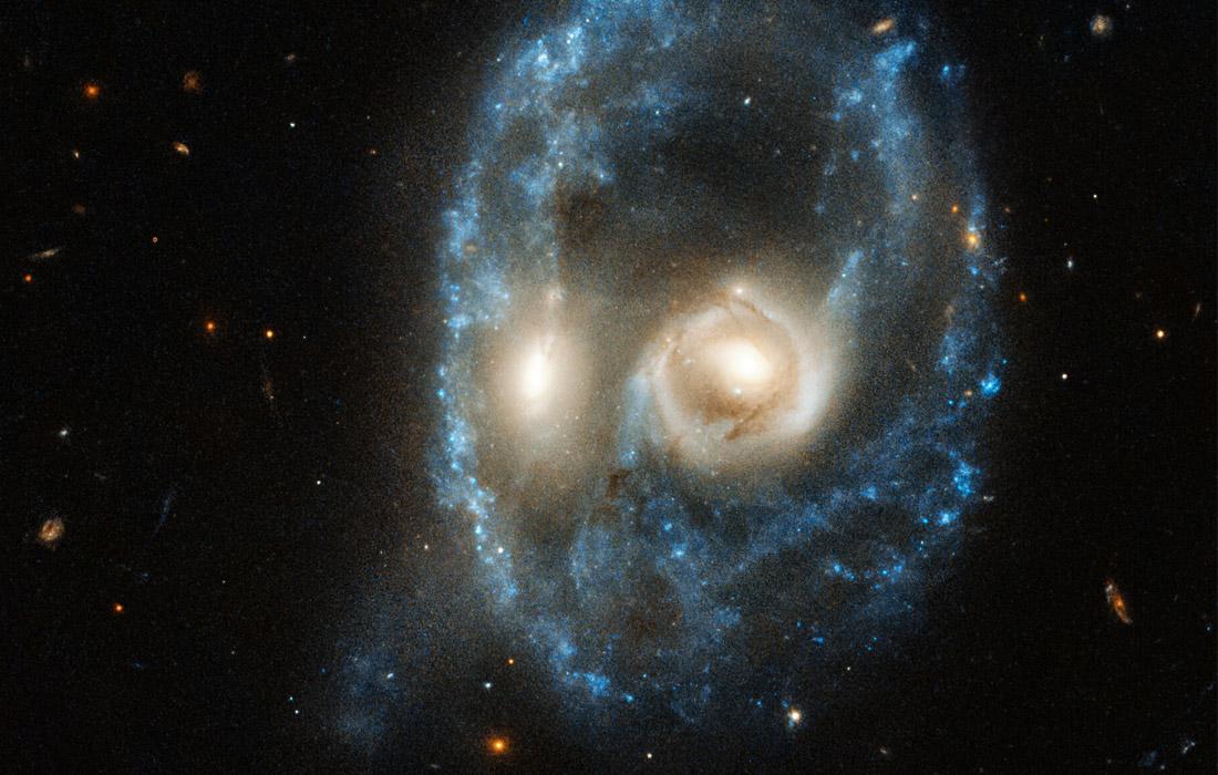 """Телескоп """"Хаббл"""" сфотографировал столкновение двух галактик, которое произошло на расстоянии около 700 миллионов световых лет от Земли. Вокруг столкновения образовалось кольцо из звездного вещества."""