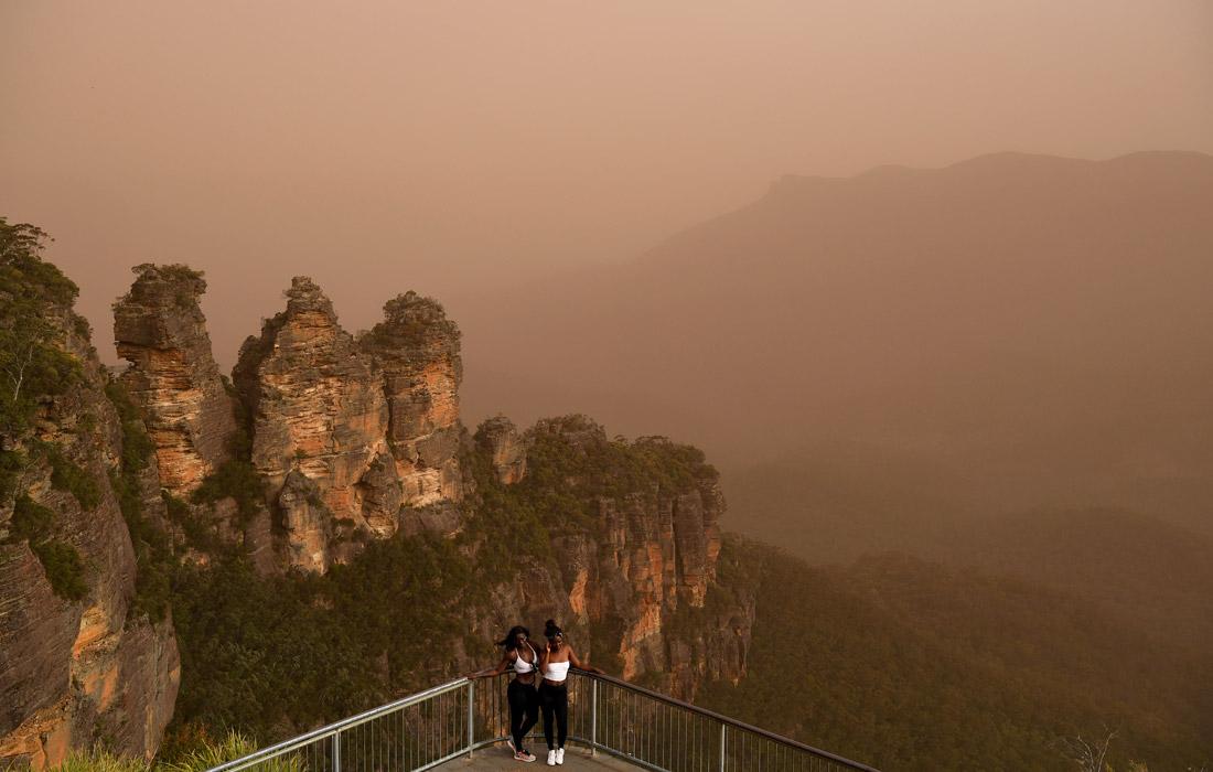 """Туристы на смотровой площадке с видом на скалы """"Три сестры"""" в Новом Южном Уэльсе"""