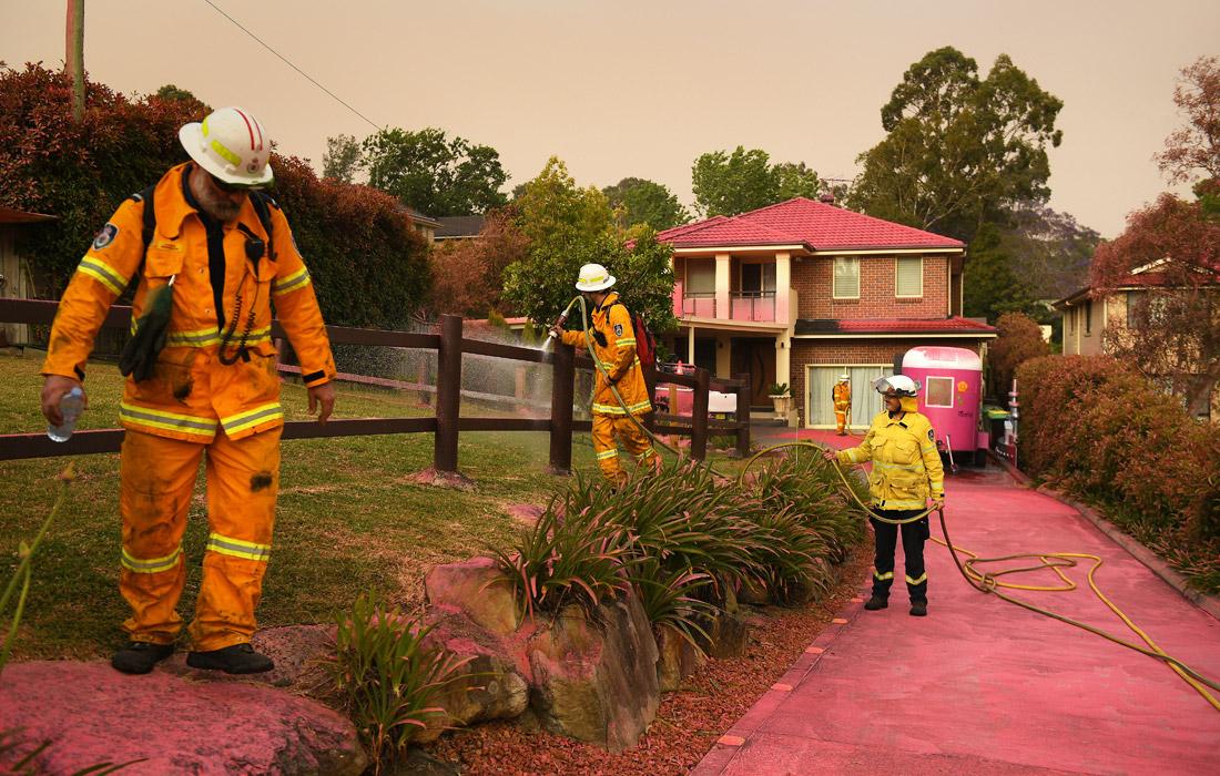 Сотрудники пожарной охраны очищают дома после распыления антипиренов - средств для защиты от огня. Новый Южный Уэльс.