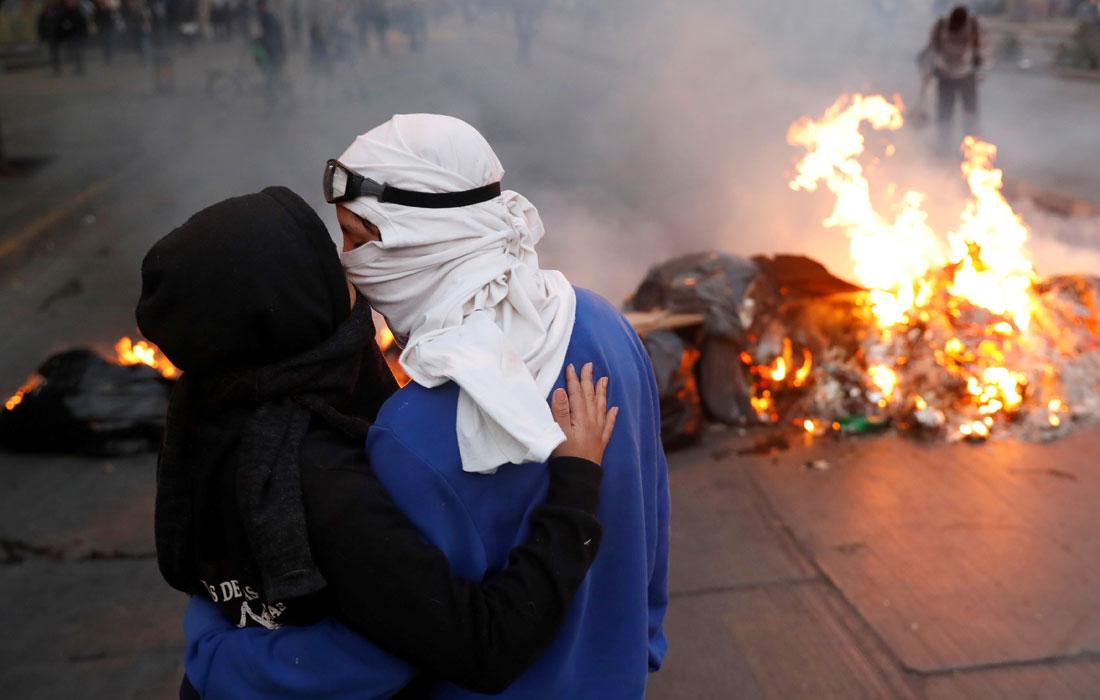 Пара демонстрантов целуется перед горящей баррикадой во время акции протеста в Сантьяго, Чили