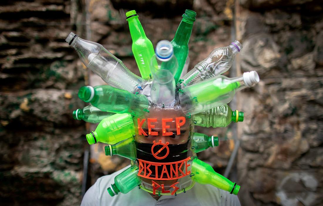 На Филиппинах число заразившихся коронавирусом превысило 15 тысяч. На фото: художник Лерой Нью в защитной маске из пластиковых бутылок в своей студии в Кесон-Сити.