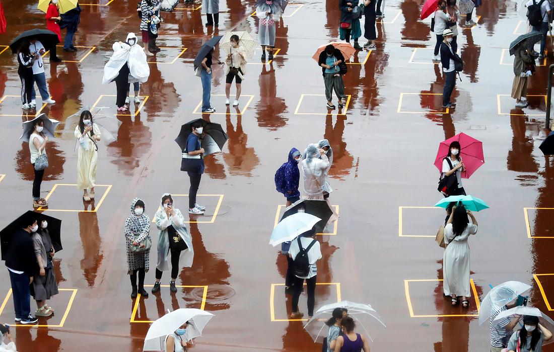 В Токио зафиксирован рекордный с момента снятия ЧС прирост новых случаев коронавируса. Общее количество инфицированных составляет около 6,4 тысяч человек. На фото: посетители у входа в Диснейленд, который открылся после четырех месяцев перерыва.