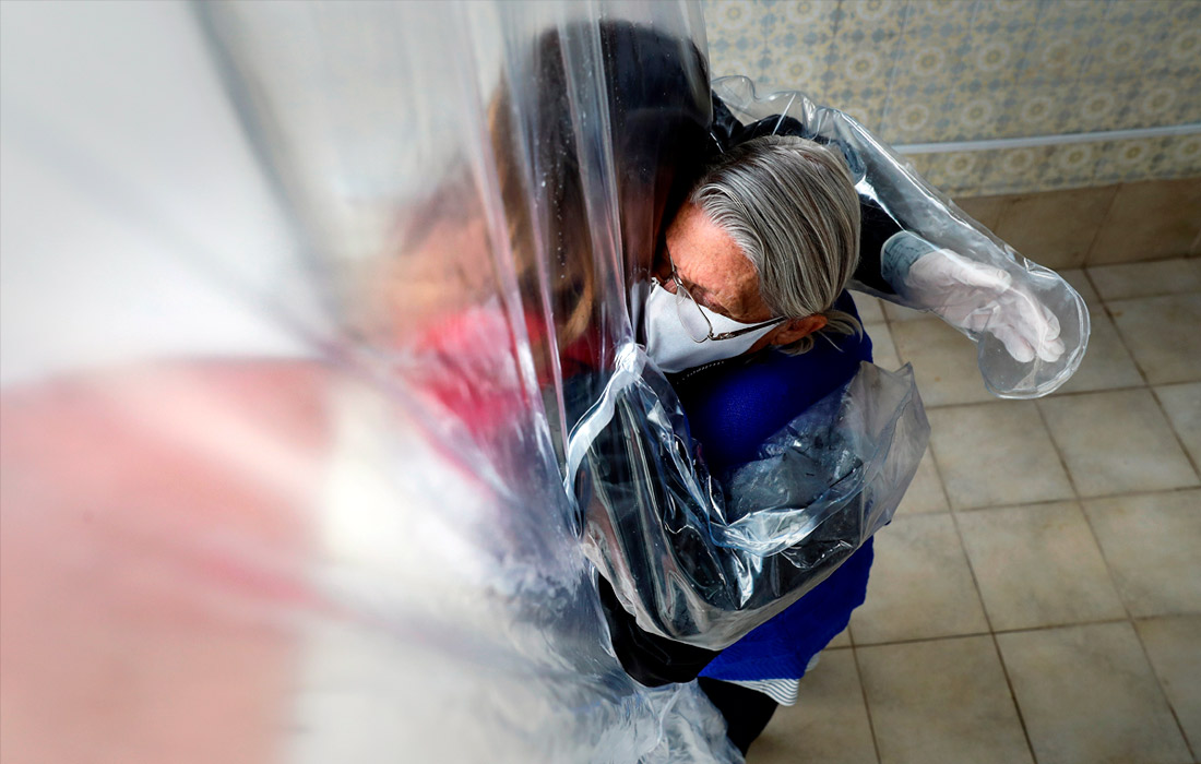 3 июля. Постояльцы дома престарелых в Сан-Паулу обнимают родных через пластиковую защиту.