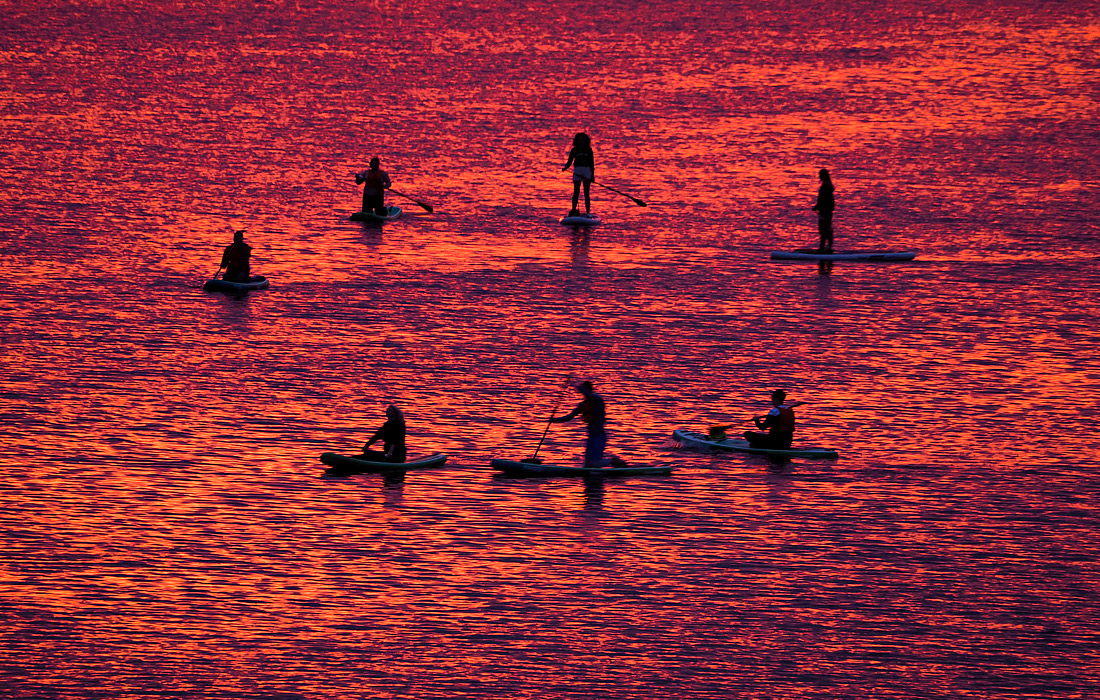 Сапсерферы во время заката на реке Великая в Пскове