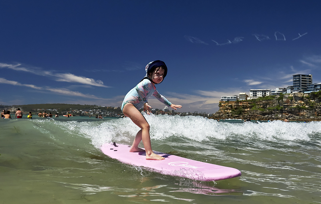 Девочка покоряет свою первую волну на пляже в Сиднее в День Австралии