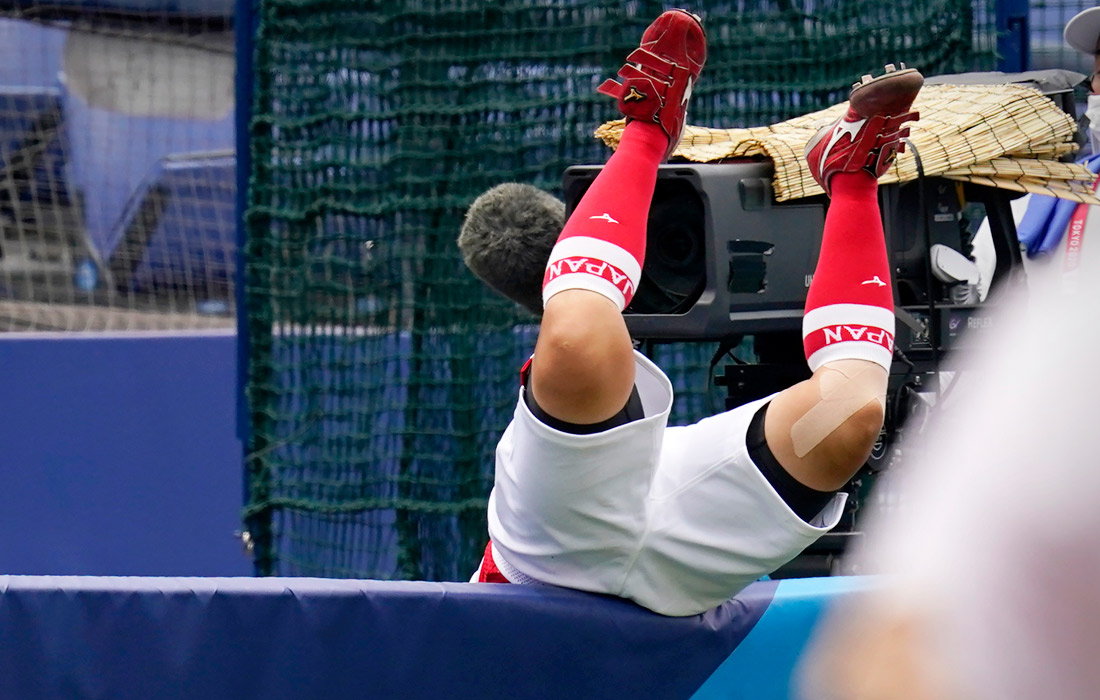 Японец Ю Ямамото перелетает через стену во время матча по софтболу