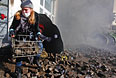 Женщина несет камни к зданию парламента Украины.