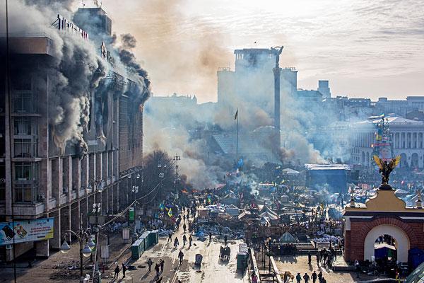Дым от пожаров и сторонники оппозиции на площади Независимости в Киеве, где начались столкновения митингующих и сотрудников милиции.