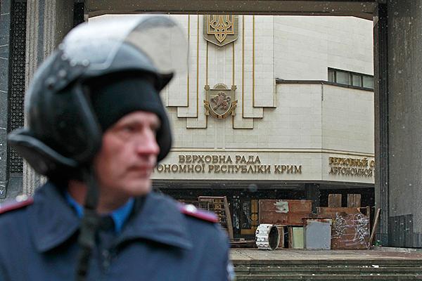 Милиционер у здания забаррикадированной Рады Крыма.