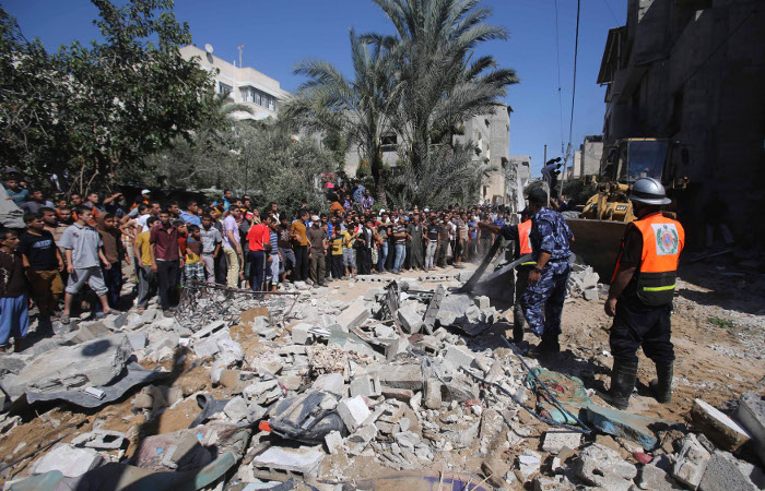 Палестинцы смотрят на дом, разрушенный авиаударом.