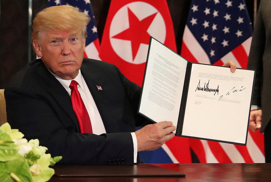 Дональд Трамп демонстрирует подписанный с Ким Чен Ыном документ после переговоров