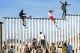 Первые беженцы попытались перелезть через ограждение на границе Мексики и США